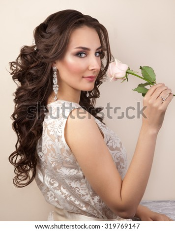 Portrait of beautiful woman with makeup and curly hairstyle in white lace dress - stock photo