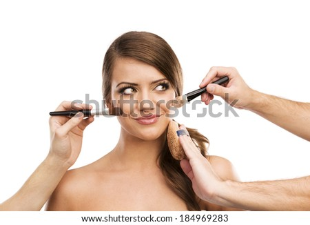 Portrait of beautiful woman with makeup brushes near attractive face, many hands applying make up on woman face isolated on white background - stock photo