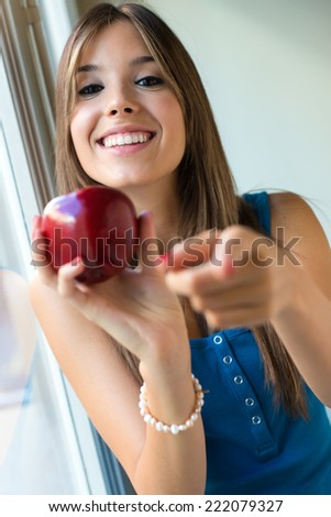 Portrait of beautiful woman with red apple at home. - stock photo
