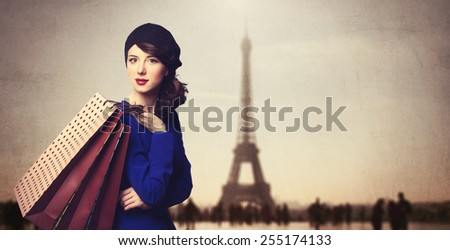 Portrait of beautiful women in blue dress with shopping bags on Parisian background. - stock photo