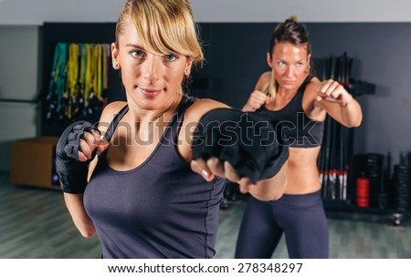 Portrait of beautiful women training hard boxing in the gym - stock photo