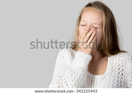 Portrait of beautiful yawning casual caucasian young woman wearing white knitted sweater, sleepy, bored or tired, studio shot, gray background, copy space - stock photo