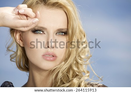 portrait of beautiful young adult attractive sexy and sensuality pretty blonde girl on background blue sunlight sky - stock photo