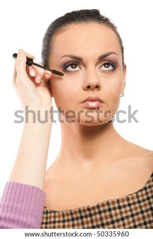 Portrait of beautiful young adult woman applying cosmetic - stock photo