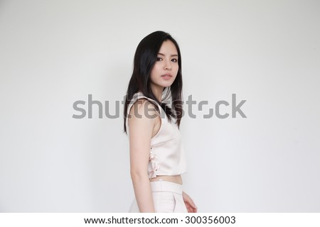 Portrait of beautiful young Asian woman in pastel pink top and pant - stock photo