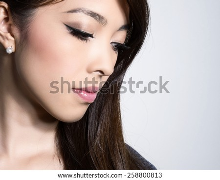 portrait of beautiful young asian woman with perfect skin and flawless make-up, lipstick, mascara and eye-shadows - stock photo