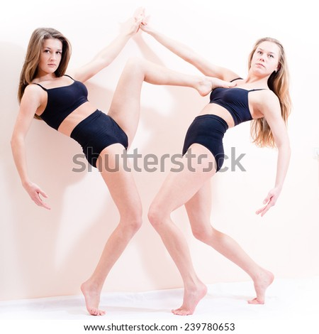 portrait of 2 beautiful young athletic woman standing on tiptoe and one of them holding foot on the chest of another on white - stock photo