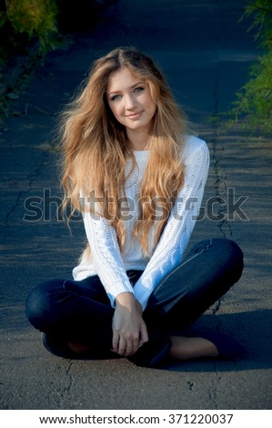Portrait of beautiful young attractive blond sitting on the road park. She wearing a white sweater and blue jeans. Warm sunny weather. Outdoor shot - stock photo
