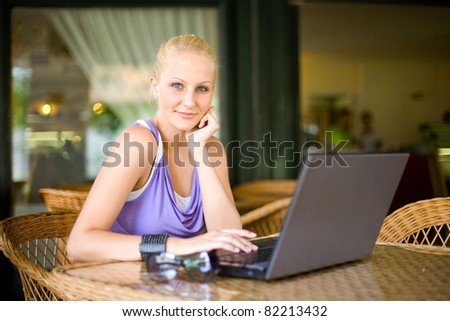Portrait of Beautiful young blond girl having fun with her laptop at a coffee shop. - stock photo