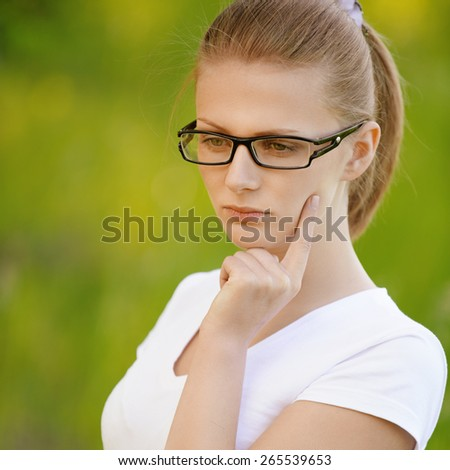 portrait of beautiful young blond thoughtful woman in eyeglasses at summer green park - stock photo