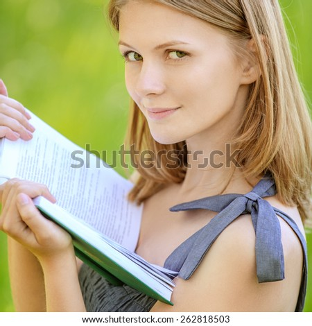 portrait of beautiful young blond woman reading book in summer green park - stock photo