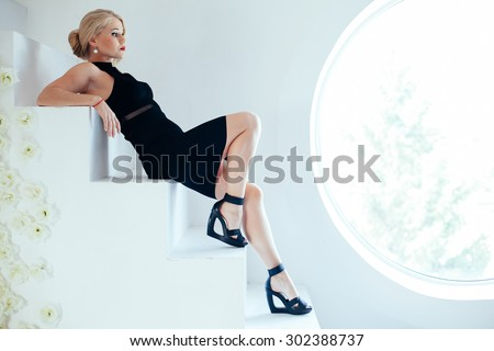 Portrait of beautiful young blonde girl with red lips in black d - stock photo