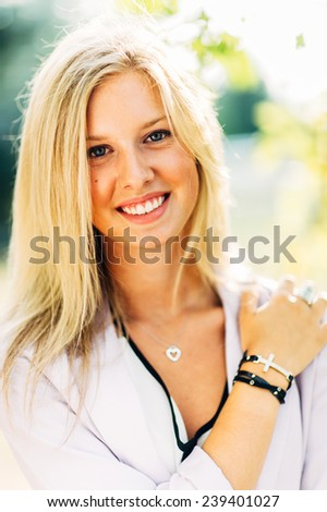 portrait of beautiful young blonde woman holding shoulder smiling - stock photo