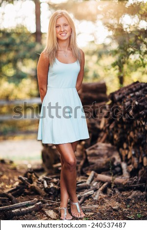 portrait of beautiful young blonde woman in front of pile of wood in dress legs crossed - stock photo