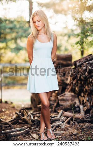 portrait of beautiful young blonde woman in front of pile of wood in dress legs crossed looking at ground - stock photo
