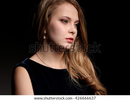 Portrait of beautiful young blonde woman on black background - stock photo