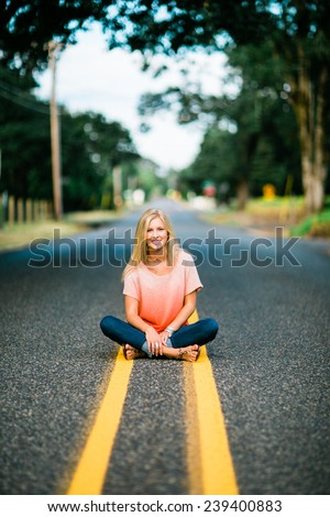 portrait of beautiful young blonde woman sitting in road legs crossed vertical - stock photo
