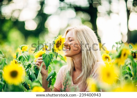 portrait of beautiful young blonde woman smelling sunflower and smiling - stock photo