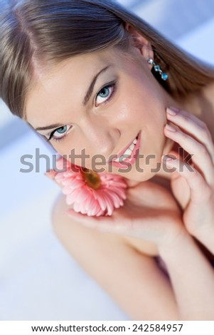 Portrait of beautiful, young, blonde woman with a pink Gerber daisy flower, head shot - stock photo