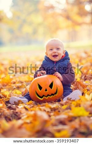 portrait of beautiful young boy holding halloween pumpkin - stock photo