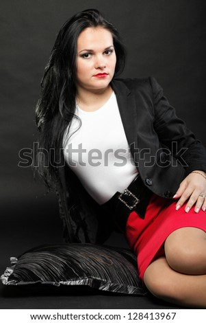 portrait of beautiful young brunette lies on black background. - stock photo
