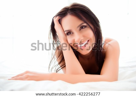 Portrait of beautiful young brunette lying in bed at home - stock photo