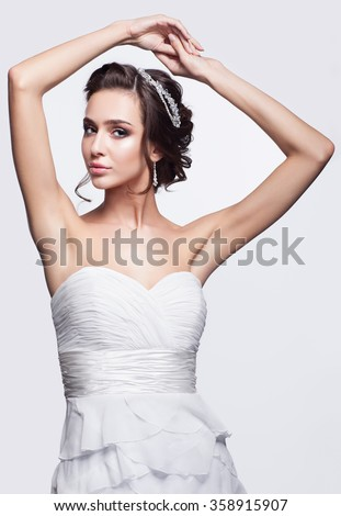 Portrait of beautiful young brunette woman bride in white Wedding Dress with hands up on light gray background - stock photo