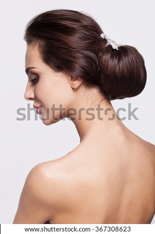 Portrait of beautiful young brunette woman from back side with knot of hair - stock photo