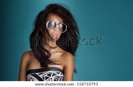 Portrait of beautiful young brunette woman posing in sunglasses. - stock photo