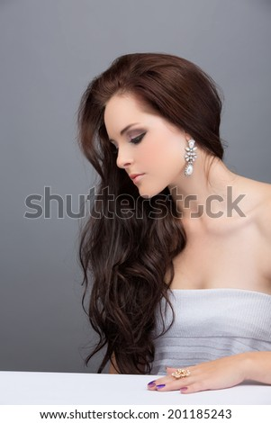 Portrait of beautiful young brunette woman. Wearing long loose curly hair. Against grey studio background.  - stock photo