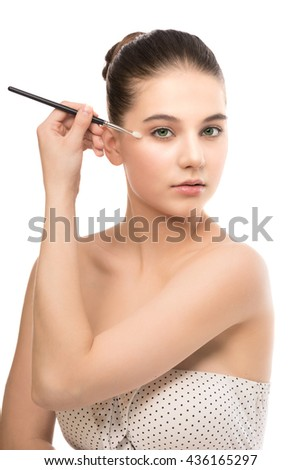 Portrait of beautiful young brunette woman with clean face. Beauty spa model girl with perfect fresh clean skin applying cosmetic brush. Youth and skin care concept. Isolated on a white background. - stock photo