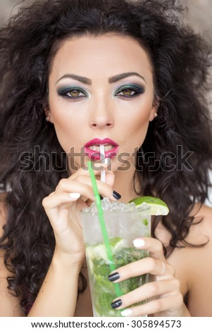 Portrait of beautiful young brunette woman with curly hair and bright makeup drinking alcoholic mojito cocktail from mint soda light rum ice cubes and lime with straw, vertical picture - stock photo