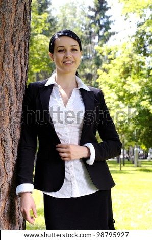 Portrait of beautiful young business woman leaning on the tree trunk in park - stock photo