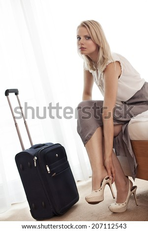 Portrait of beautiful young businesswoman removing high heels in hotel room - stock photo