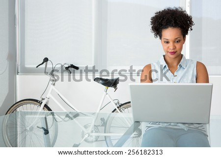 Portrait of beautiful young casual woman using laptop in office - stock photo