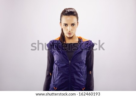 Portrait of beautiful young caucasian fitness woman wearing sportswear looking at camera while standing on grey background. Pretty young and confident female athlete with copyspace. - stock photo