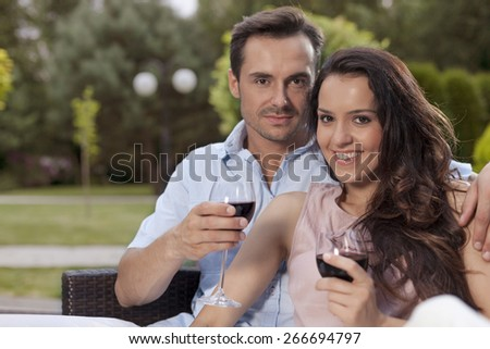 Portrait of beautiful young couple having red wine in park - stock photo