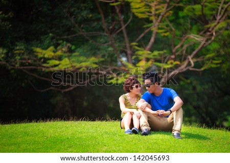 Portrait of beautiful young couple sitting on ground in park relaxing - stock photo