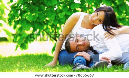 Portrait of beautiful young couple sitting on the grass in the park in sunny weather - stock photo