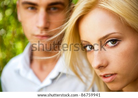 Portrait of beautiful young couple standing against green tree in park relaxing - stock photo