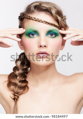 portrait of beautiful young dark blonde woman with creative braid hairdo touching temples - stock photo