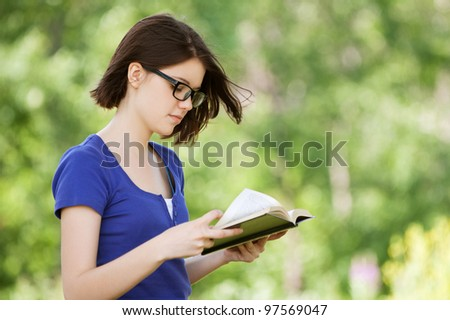 Portrait of beautiful young dark-haired pretty girl reading book at summer green park - stock photo