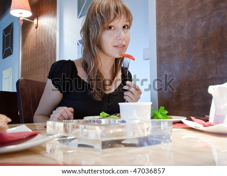 portrait of beautiful young eating girl in restaurant interior - stock photo