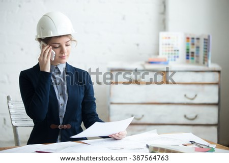 Portrait of beautiful young engineer woman in white helmet sitting at office desk in architectural agency using smartphone. Attractive model making call holding project plan, planning work - stock photo
