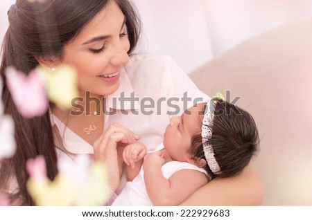 Portrait of beautiful young female holding on hands cute newborn daughter, enjoying motherhood, soft focus, happy family concept - stock photo