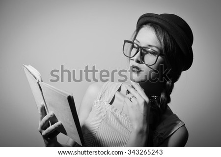 Portrait of beautiful young female in hat and glasses reading a book. Black and white photography  - stock photo