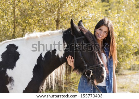 portrait of beautiful young female rider embracing her horse and looking at camera - stock photo