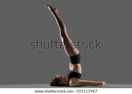 Portrait of beautiful young fit woman in sportswear doing sport exercises for shoulders and neck, niralamba sarvangasana posture, full length, profile view, studio image on gray background - stock photo