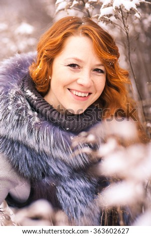 Portrait of beautiful young girl dressed in fur coat at winter trees background. Beauty woman having fun outside on winter snowy day. Close up of female smiling face with gorgeous long red hair.  - stock photo