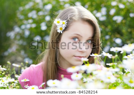 portrait of beautiful young girl in a meadow with camomiles - stock photo